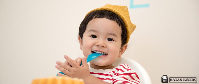 Bayi sedang menggunakan peralatan makan