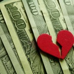 Broken red heart on assorted cash