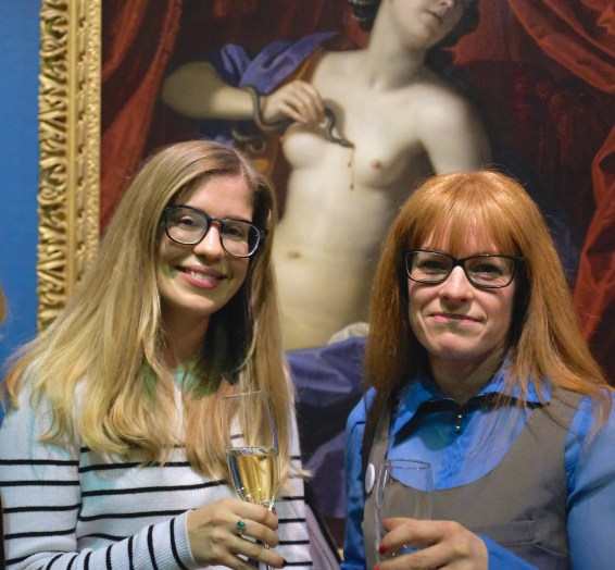 Lauren Gardner and Emma Read holding champagne glasses in front of a large painting in an ornate gilt frame