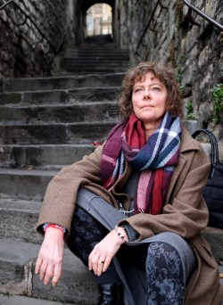 Author Jaqueline Haskell sitting on stone steps in Walcot, Bath