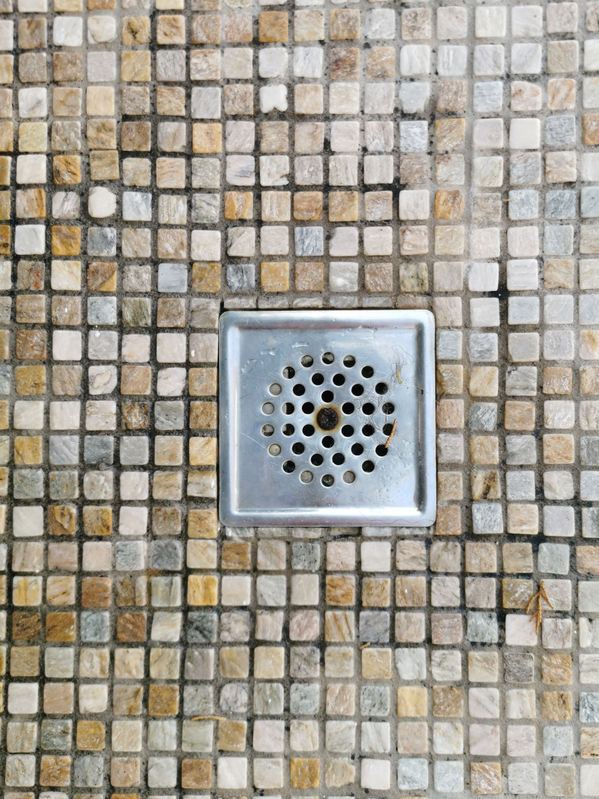 plum hole for the shower in the floor with a small mosaic