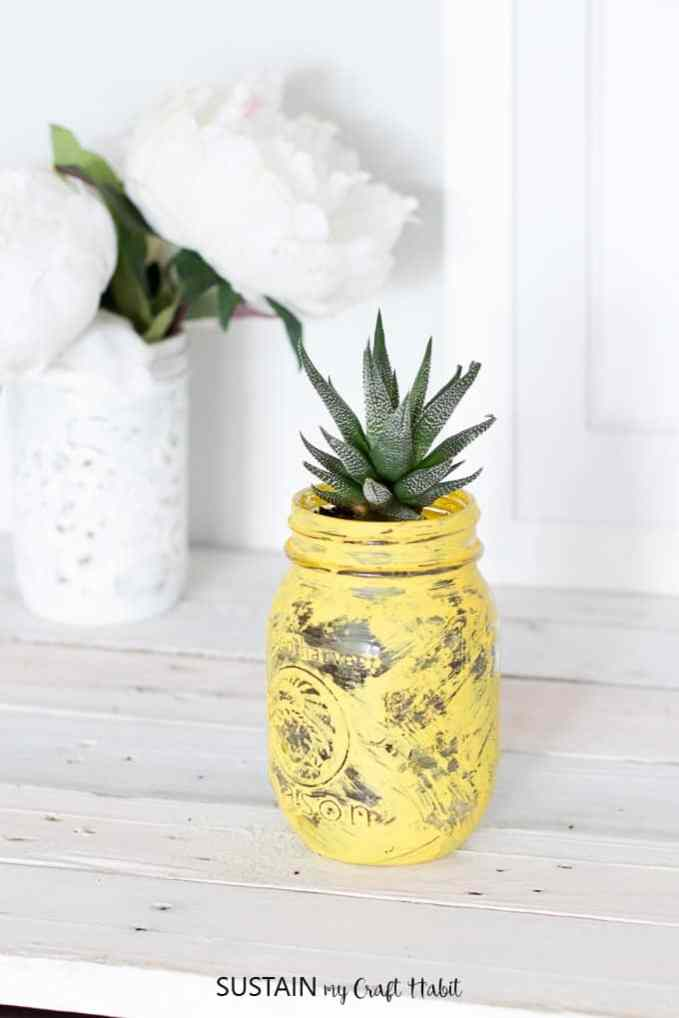 A yellow mason jar with a succulent that looks like a pineapple.