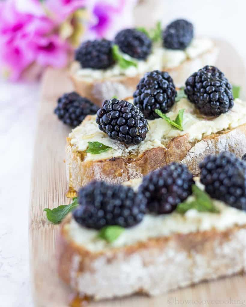 Blackberries and mint leaves on top of goat cheese toast.