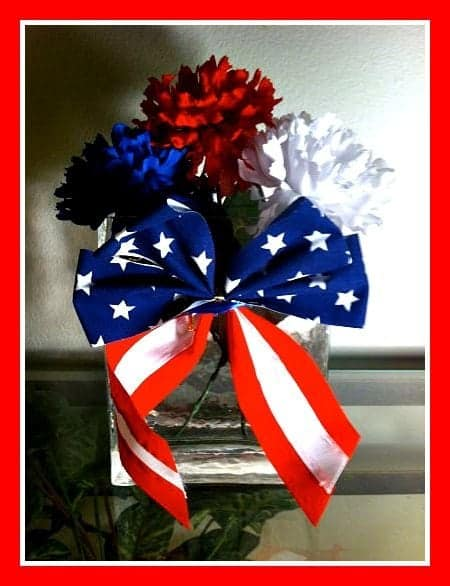 Red white and blue flowers with and American flag ribbon around the vase.