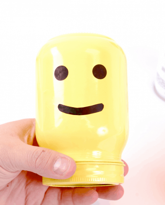A painted yellow mason jar with a face that looks like a Lego man.