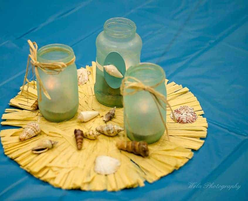 Three frosted glass jars with raffia and seashells.