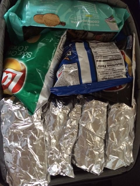 Hot dogs wrapped in tin foil and some bags of chips.