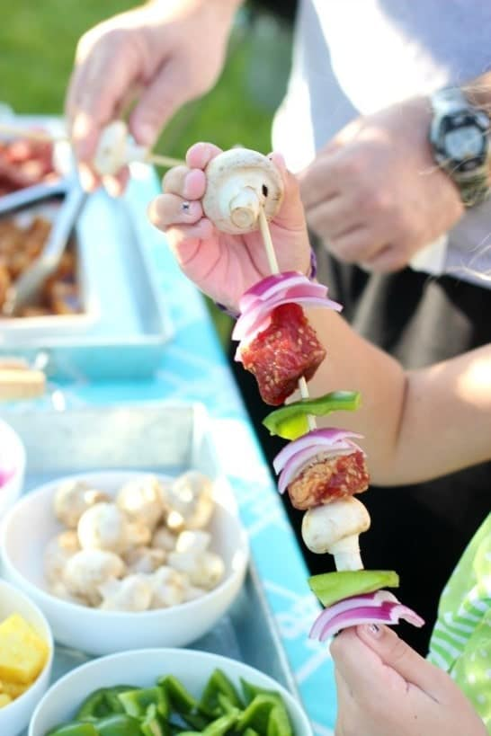 A person assembling a meat and veggie kabob.