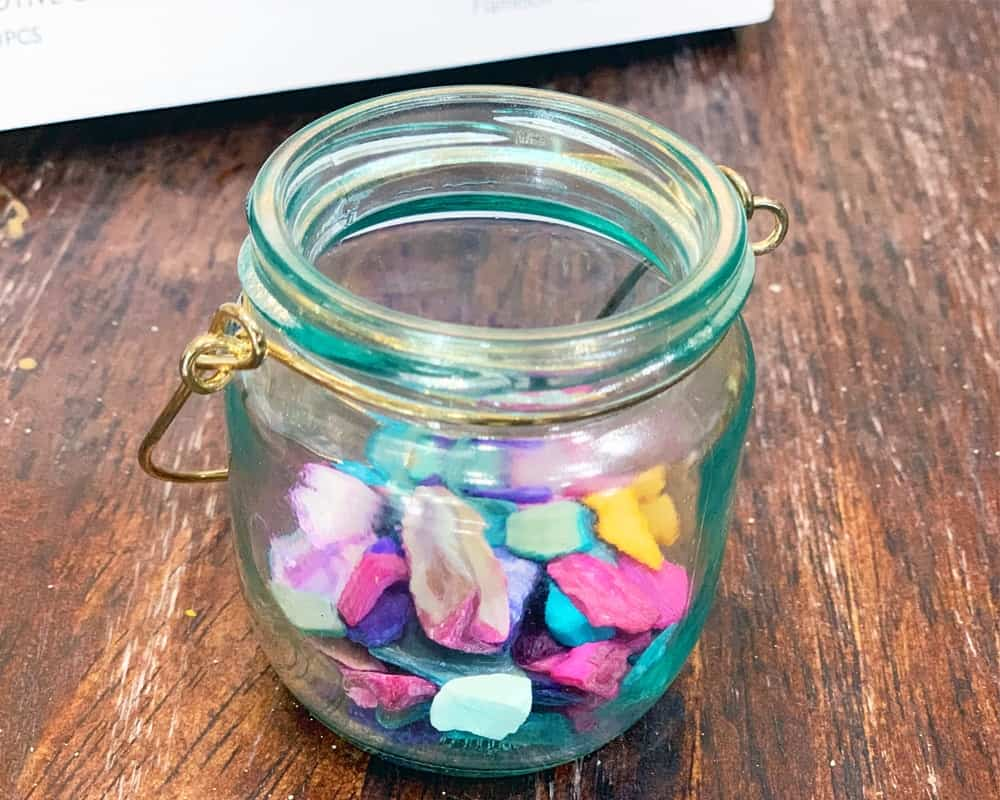 Little mason jar filled with colorful rocks.