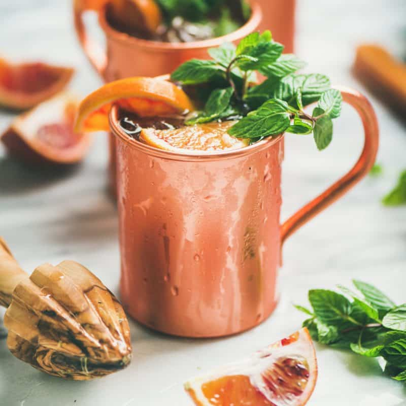 Orange and mint leaves in a copper Moscow mule cup