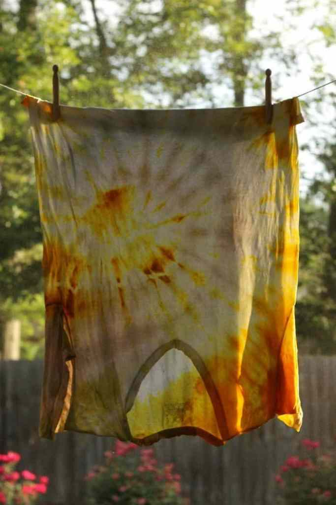 a shirt hanging in the sun tie dyed with yellow turmeric