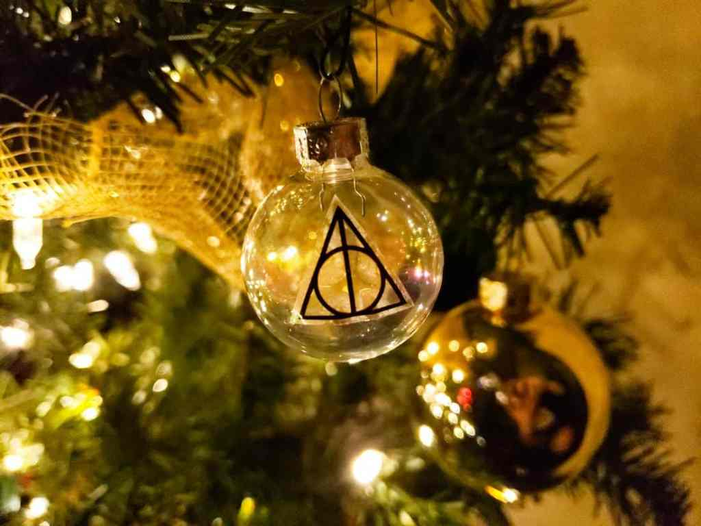 A clear ball ornament with a deathly hollows symbol on it.