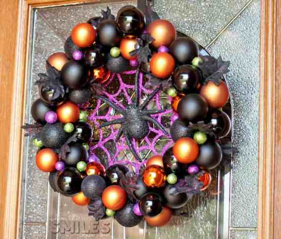 A DIY Halloween craft wreath made out of Halloween colored balls