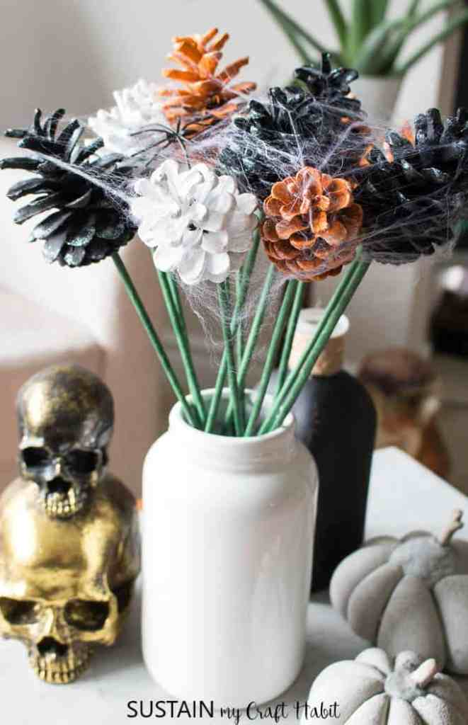 A white vase with a spooky pine cone bouquet