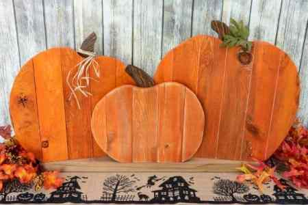 Three orange wood pumpkins made out of palettes