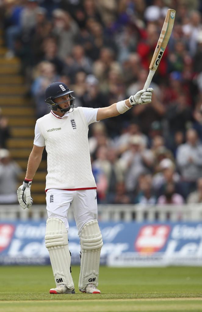 Root raises his bat upon reaching his half-century