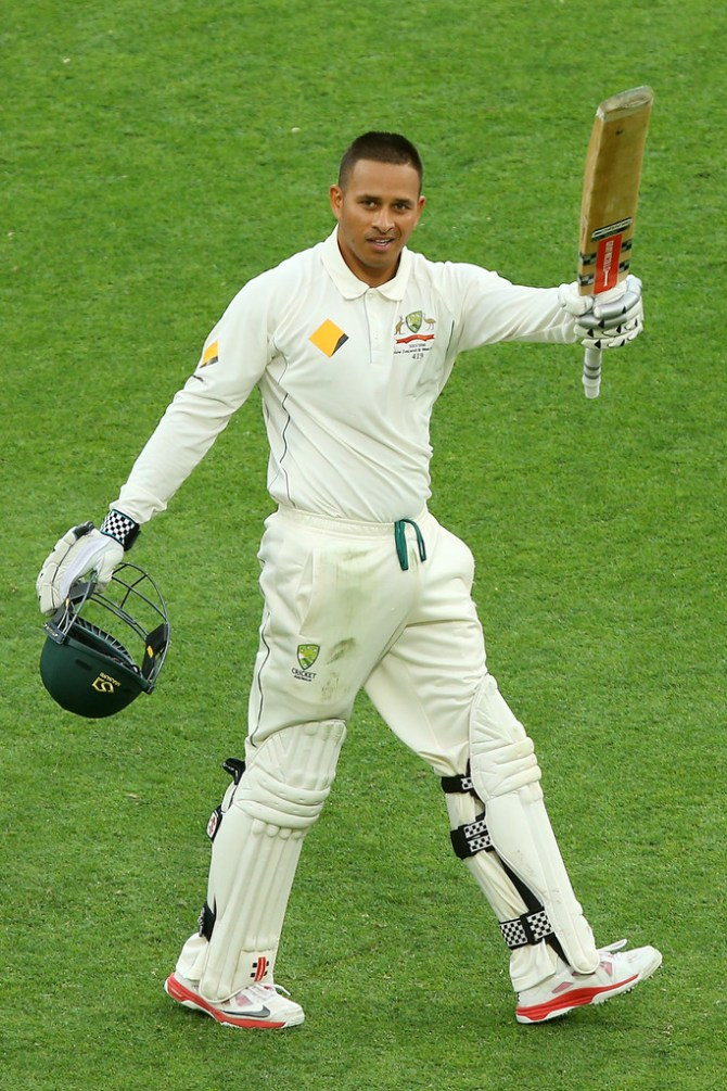 Khawaja raises his bat after bringing up his maiden Test century