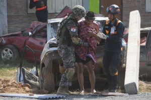 Military medics and soldiers tend an injured civilian