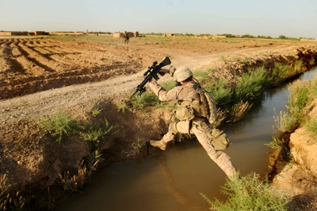 Cpl. James Kirkpatrick, of Kilo Company, 3rd Battalion, 6th Marines, makes a long leap across a canal east of Marjah, Afghanistan while on patrol May 24. Kirkpatrick's squad was later attacked during that same patrol in a coordinated attack. (Thomas Brown/Staff)