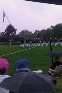 The Silent Drill Team marches in front of the Iwo Jima Memorial. Gale winds, sheets of rain and thunder and lightening cut the Sunset Parade short on July 13. (Photo by Gina Cavallaro)