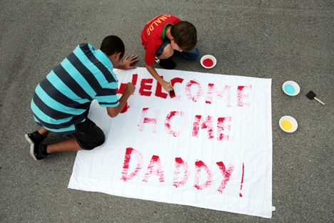 Kenneth Berregard, left, and his brother Kevin paint a welcome home banner for their father, Gunnery Sgt. Kenneth Berregard, at a Combat Logistics Battalion 6 banner-making event July 17 at the Camp Lejeune, N.C., base stables. (Photo by Sgt. Jeremy Ross/Marine Corps)
