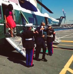 President Barack Obama salutes Marines with a coffee cup in his hand.