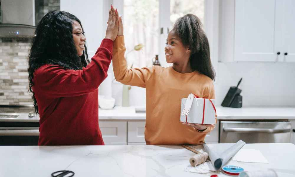 Black woman giving high five to daughter