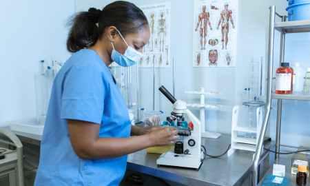 Black woman looking under microscope in hospital gear