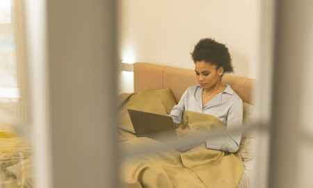 Black woman on bed working on laptop