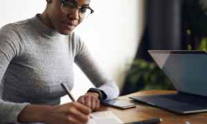 black woman writing while working on computer