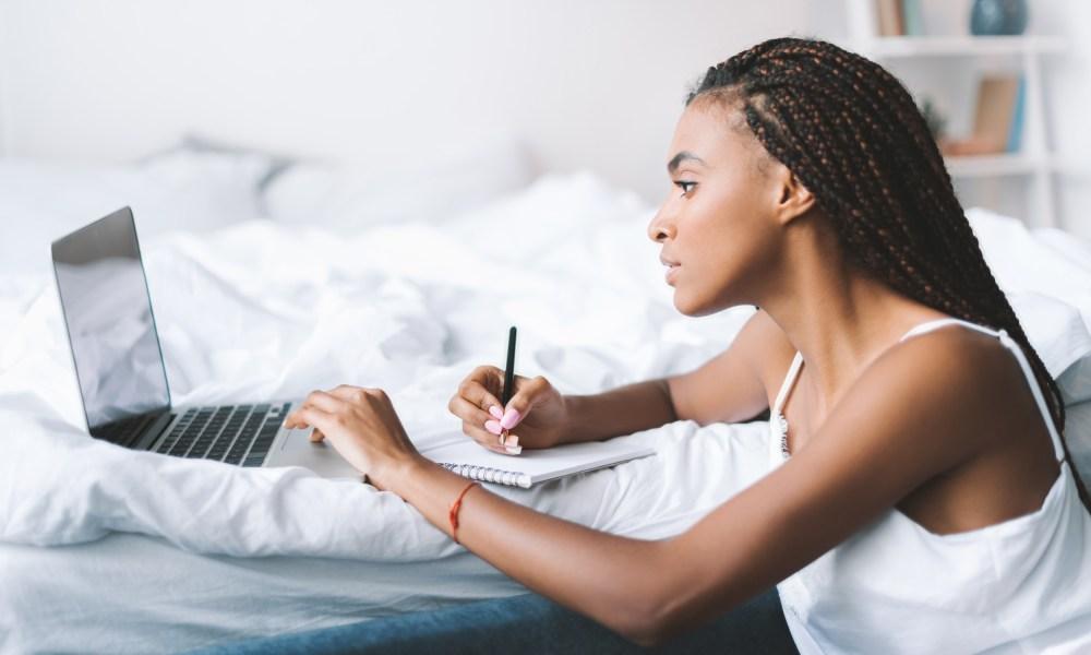 black woman writing student cv resume