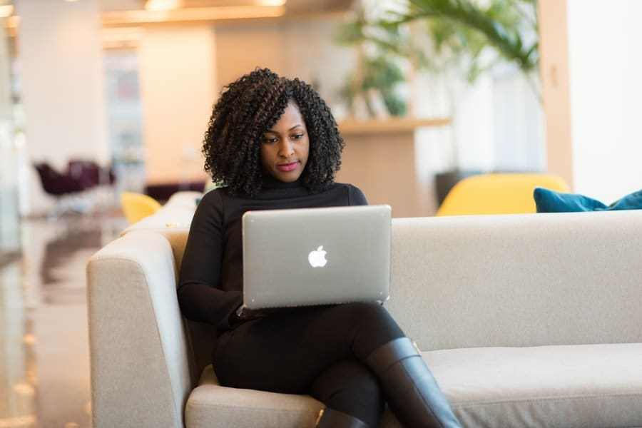 black woman doing work on her computere whil sitting on couch