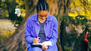 black woman writing in journal in the park