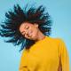 happy black woman wearing yellow sweater