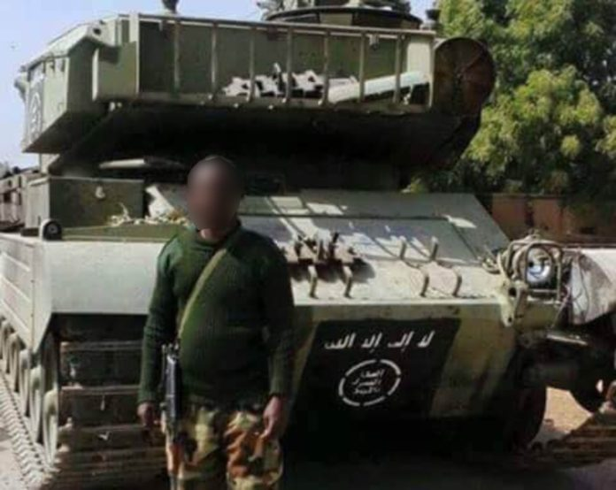 A Nigerian soldier standing in front of recovered sophisticated Armoured Battle Tank from terrorists in 2015