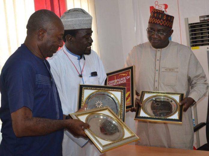 Editor-in-Chief Ewache Ajefu, and Yushau Shuaib of PRNigeria presents the multiple awards to NIPR Chief, Mukhtar Sirajo