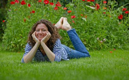 Zufriedene Gärtnerin auf sattgrünem Rasen - Rasen im Frühjahr