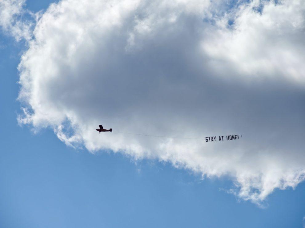 Stay at Home - Flugzeug mit Corona Banner am blauen Himmel über der Bauernhof Kita