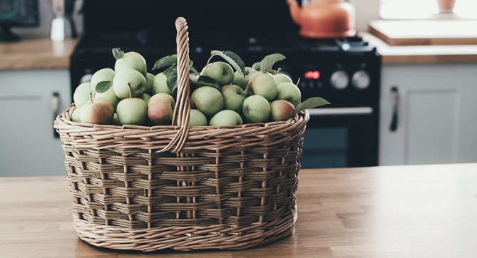apples in a basket on a kitchen counter