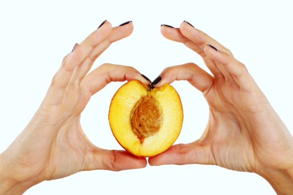 Peach fruit in woman's hands isolated