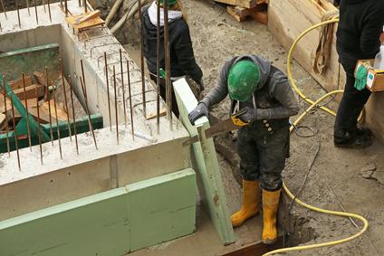 Ein Bauarbeiter bringt eine XPS Platte an.
