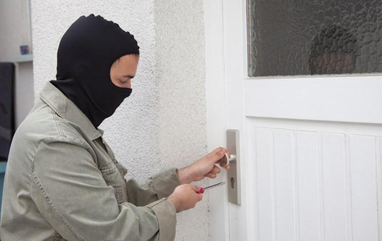Ein Einbrecher macht sich am Beschlag der Haustür zu schaffen