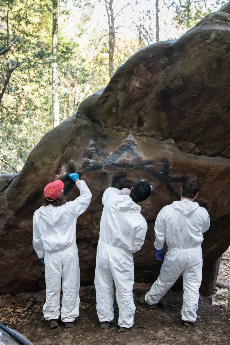 three volunteers prepare a rock for graffiti removal by applying a thick, pasty paint remover