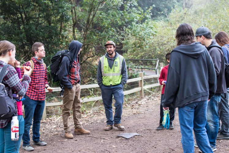 Volunteers gather around a Parks and Recreation employee to discuss brush removal tasks