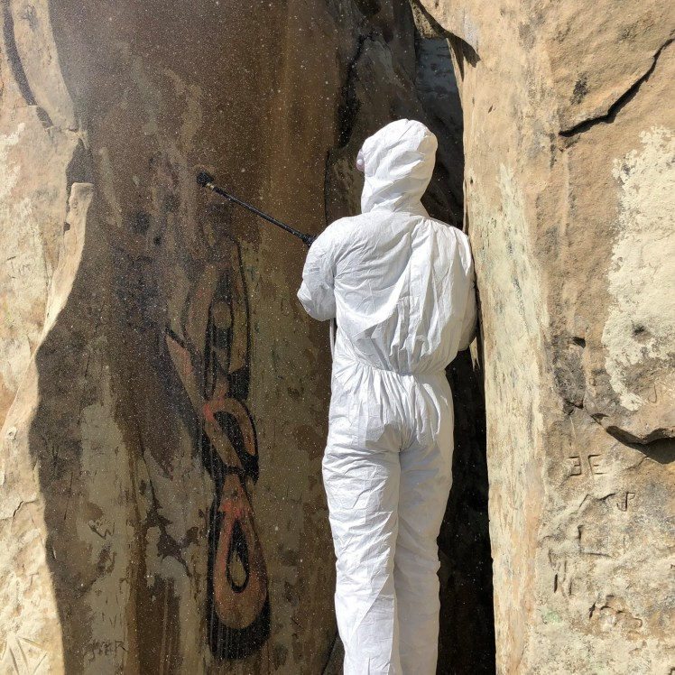 a volunteer wearing a tyvek protective suit washes graffiti away from the rock