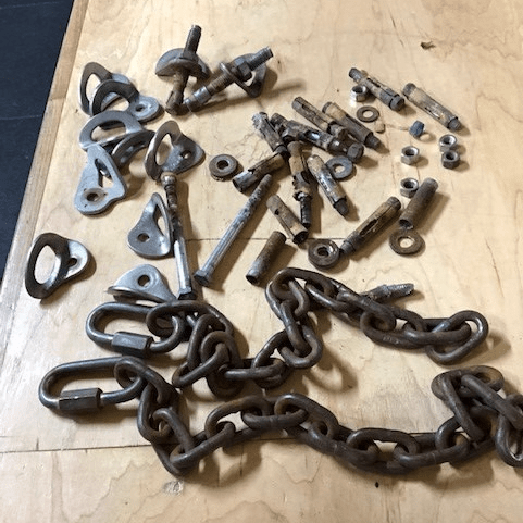 a collection of old bolts, hangers, and chains removed from climbing routes