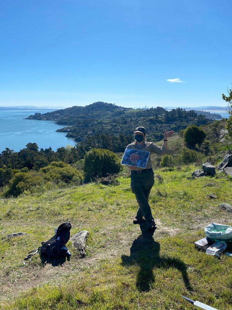 A masked Marin County Parks official holds a map of the park out for their audience to see while speaking to the group, un-pictured. At their feet is a backpack and cleanup-related supplies. A beautiful view of Tiburon is in the background. The San Francisco and Oakland cityscapes are faintly visible in the far background.