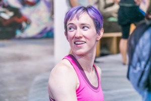 A side portrait of Maggie looking behind her shoulder. The background is blurred. Her hair is a bright purple and she is wearing a pink tank top.