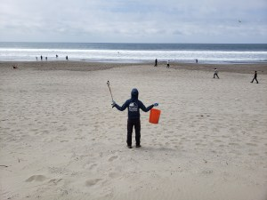 A volunteer raises their arms in triumph while looking at a beach they've successfully cleaned. Several patrons of the beach are walking in the background.