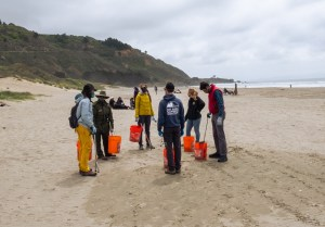 Volunteers from the Bay Area Climbers Coalition stand on a beach with buckets and grabbers in their hand while listening to instructions from a National Park Service ranger